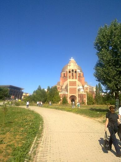 Taip ir neužbaigta statyti cerkvė šviesioje suremontuotoje aikštėje (Priština)