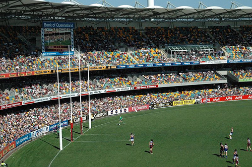Milžiniško apvaliojo stadiono šonas ir trigubi vartai su keturiais skersiniais. Žaidėjai pasklidę po visą aikštę - vienu metu kiekvienoje komandoje jų žaidžia net po 18.